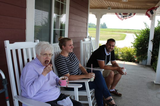 Customers sit out on the porch at Kelley's Creamery where they enjoy ice cream made with the milk of the family's herd of cows just across the field. Since opening this spring, the family only offers outside service and carryouts.