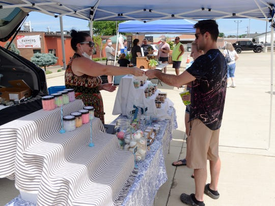 April Lentz, of Thacker Hollow Studios, sells artisan soap to a customer last Saturday at the Zanesville Farmers Market at Adornetto's Select Italian Foods. Lentz is one of numerous local vendors who sells products at the market.