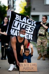 Willie Coman, of Cincinnati, kneels for a photo with his 4-year-old son, Willie Jr., May 31, 2020.
