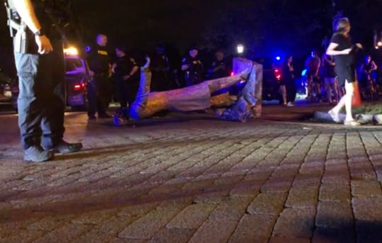 In this image from video, police stand near a toppled statue of Jefferson Davis on Wednesday night, June 10, 2020, in Richmond, Va. Protesters tore down the statue of Confederate President Davis along Monument Avenue. The statue in the former capital of the Confederacy was toppled shortly before 11 p.m., news outlets reported. (WWBT-TV via AP) ORG XMIT: NYDB711
