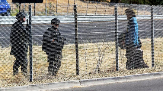 Police officers talk to a man on Thursday along U.S.Highway 101 in Paso Robles, Calif., as part of a full-scale investigation into the shooting of a sheriff's deputy early Wednesday.