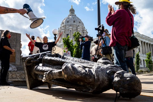 Mike Forcia raises his hands in the air as people photograph the fallen Christopher Columbus statue at the Minnesota State Capitol in St. Paul, Minn., Wednesday, June 10, 2020.
