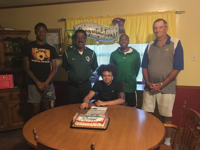 Peabody's Michael Kaiser (center) signed to play post-graduate ball with Feltrim Academy in Florida Thursday. From left are Peabody senior and Paul Quinn signee Andrew Pearson, coach Charles Smith, Kaiser, assistant Kedric Smith and Kaiser's grandfather and former Pineville coach, Ronnie.