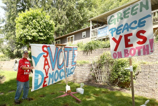 Robin Dirk Hordon turns one of the homemade political signs in the front yard of his Kingston home on Thursday.