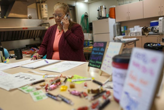 Ruby Blake makes a call while waiting for people to come get free sack lunches from the West Side Improvement Club on June 11, 2020.