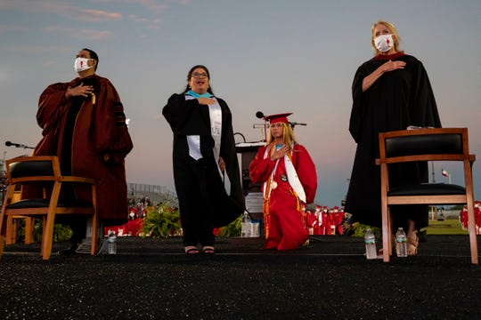 Ray High SchoolÕs valedictorian Annika McBath kneels during the National Anthem during their 2020 commencement ceremony at Cabaniss Stadium on Thursday, June 11, 2020.
