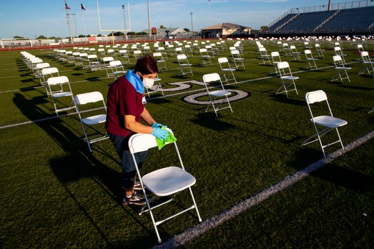 CCISD employees clean between Moddy High School's and Ray High School's 2020 commencement ceremony at Cabaniss Stadium on Thursday, June 11, 2020.