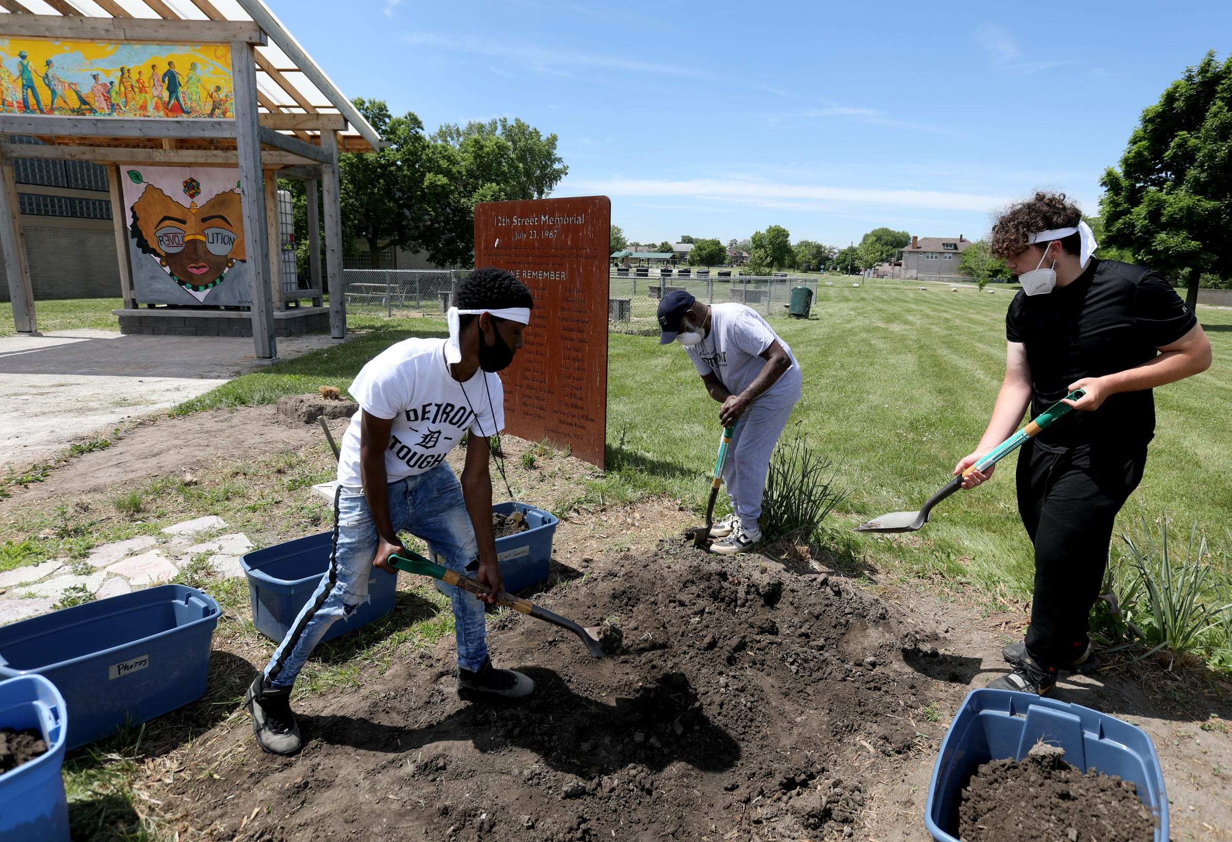 (L to R) Jeremiah Alexander, 14, Julian Witherspoon and Matthew Cole, 14, work at redoing the 12th Street memorial garden in Detroit, Michigan on Tuesday, June 9, 2020. Alexander and Cole live in the neighborhood and were asked by Witherspoon to help out in the garden as he talk to them about the 1967 riots that happened in their neighborhood.