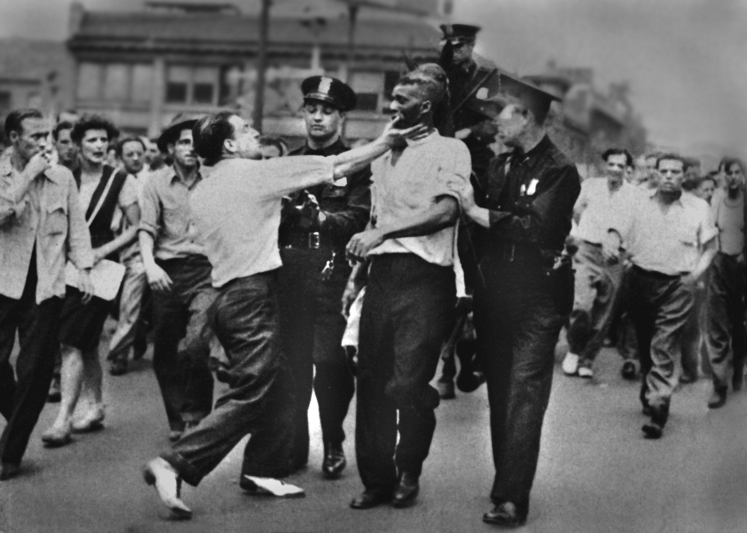 During the race riot of 1943 George Miller slaps Sam Mitchell while police lead the wounded man along Woodward Avenue. Free Press File Photo