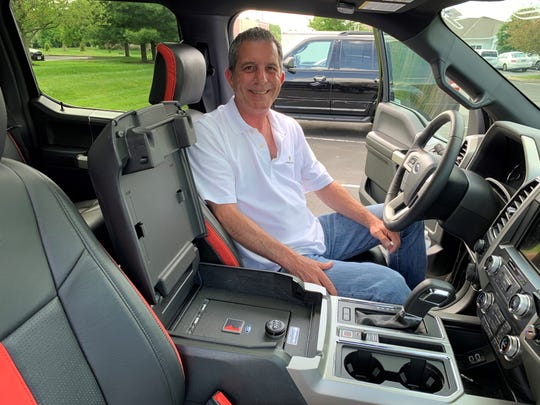 Scott Bonvissuto, co-founder of Columbus-based Console Vault, is pictured here Tuesday in his 2019 Ford F-150 pickup. He is seeing a surge in business since COVID-19. The vault is popular among pickup truck and SUV owners.