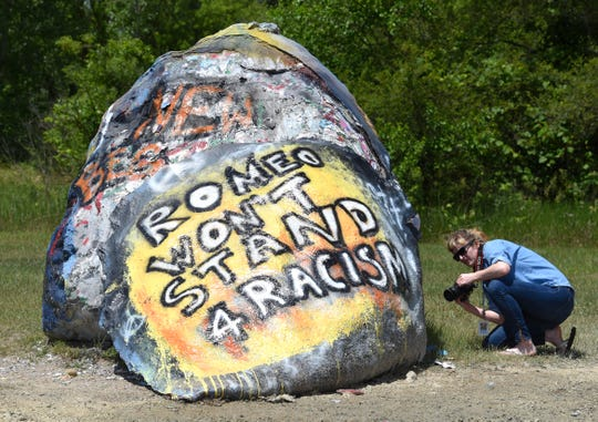 Freelance photographer Heather Sejnowski, of Ferndale, takes pictures of The Romeo Rock prior to the Romeo March Racial Justice.  Supporters march for racial justice and an end to police brutality on Main Street in downtown Romeo, Friday afternoon, June 12, 2020, before arriving at Romeo Park for a vigil with speakers from the community. The event is also in response to an incident earlier this week in which The Romeo Rock was defaced with racist remarks.