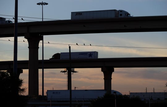 Trucks travel to and from the World Trade Bridge, in Laredo, Texas, on the U.S.-Mexico border. Carmakers are just now getting clarity on the NAFTA replacement that takes effect July 1.
