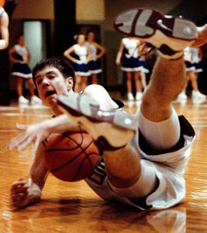 Henderson County's Brandon Fisher tries to call for a timeout as he slides across the floor during the second half of action against Caldwell County in the 1999 Second Region Tournament at Hopkinsville High School.