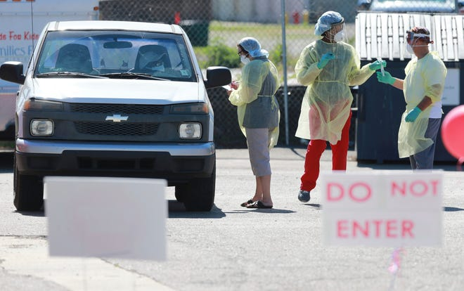 In this Thursday, June 11, 2020 photo, technicians begin gathering samples from area residents as part of a free COVID-19 testing center at the Family Resource Center on South Church Street in Tupelo, Miss.