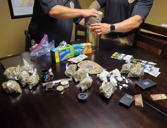 Medina Police log evidence after a narcotics search warrant that yielded four ounces of cocaine, around two lbs. of marijuana and a firearm.
