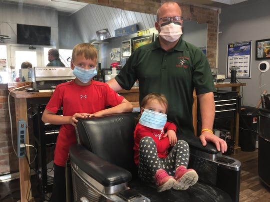 Barber Dan Huhman gathers with son Emmett, 10, and daughter Rowan, 3, inside Lonnie's Barber Shop in Pinckney, Friday, June 12, 2020. He plans to reopen the barber shop, which he owns with his father, Tuesday.