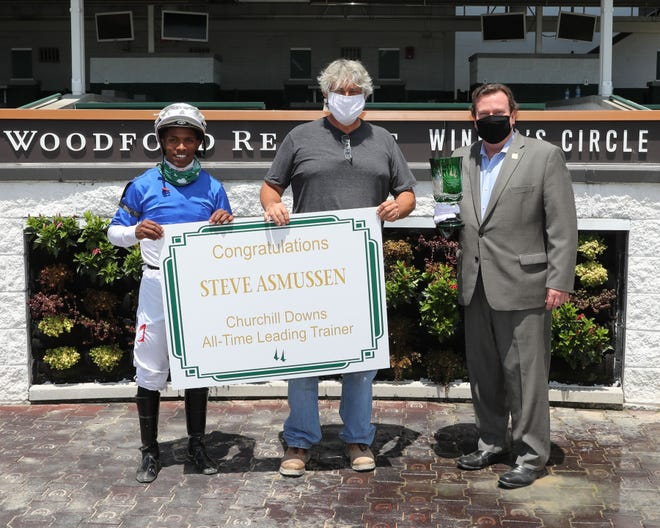 Steve Asmussen (center) was presented a sign by Churchill Downs President Kevin Flanery (right) after Drop Dead Gorgeous and jockey Ricardo Santana Jr. (left) won Friday's first race at Churchill Downs. The victory was No. 738 for Asmussen at Churchill, making him the track's all-time winningest trainer.