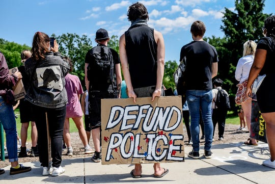A protester hods a sign reading 'Defund Police' during a demonstration against police brutality and racial injustice on at the rock on the MSU campus on Friday, June 12, 2020, in East Lansing. About 50 people marched from the rock to the East Lansing Police Department were they sat on Abbot Road in protest.