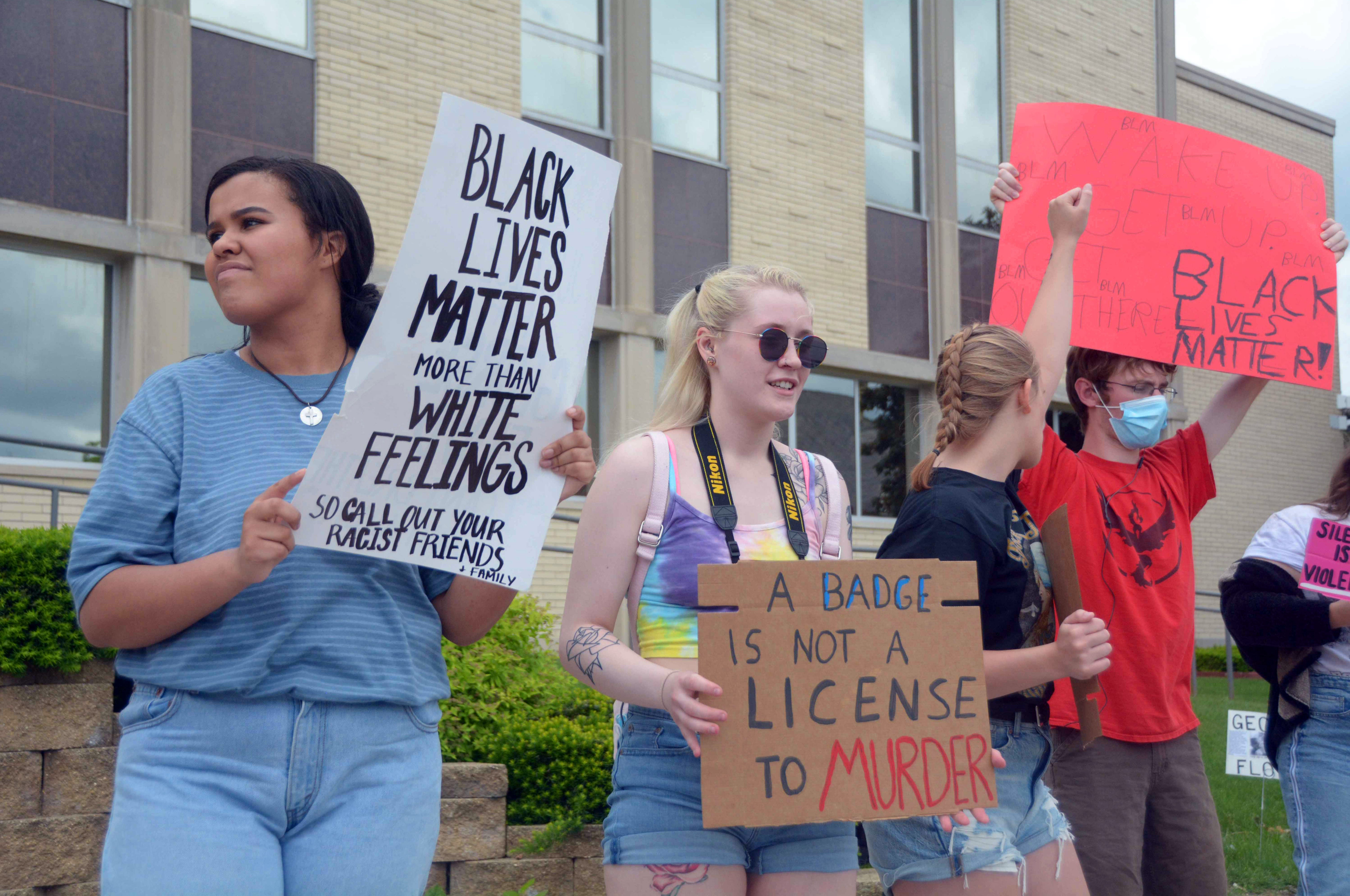 """Protest organizers Lydia Biehl and Taylor Winiecki raise signs and fists in solidarity during the Black Lives Matter protest Friday outside the Columbia County Courthouse in Portage. """"We just decided we needed to do this here,"""" Schumann said."""