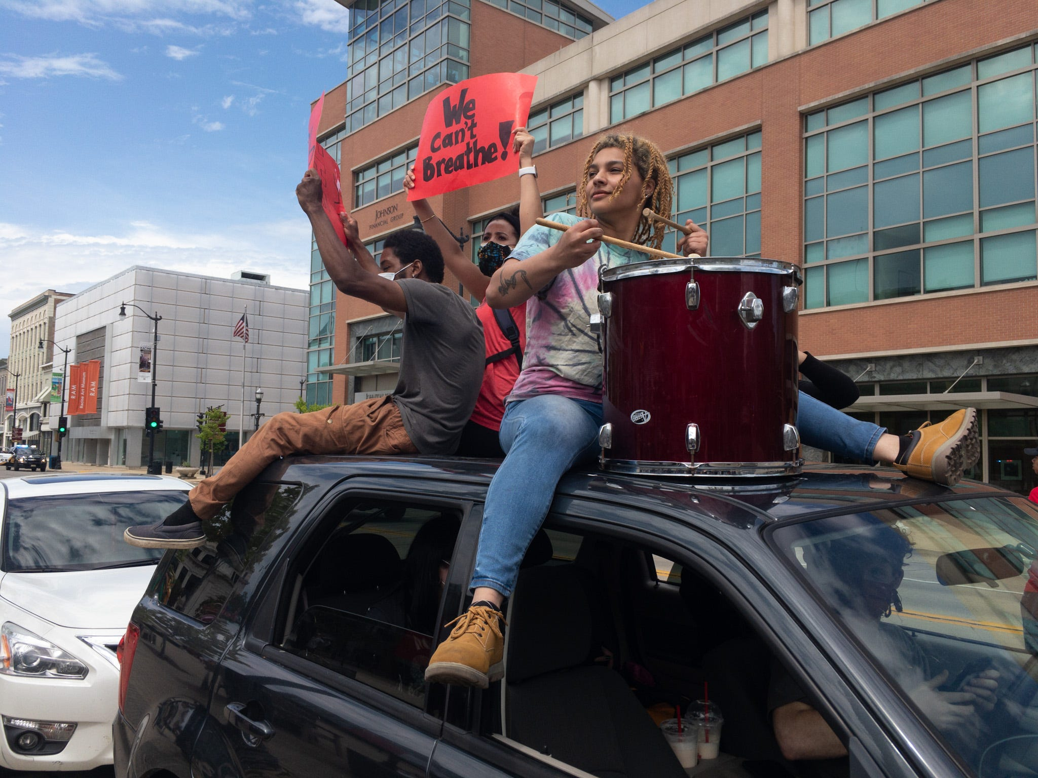 Olivia Owens bangs a drum while riding atop a vehicle in Racine on during a protest decrying police brutality following the death of George Floyd.