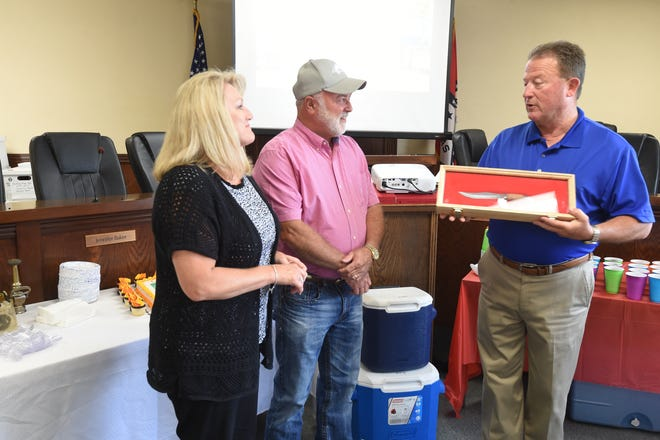 Mountain Home Fire Chief Ken Williams, center, and his wife Laura, left, smile as Mayor Hillrey Adams present them with a knife during a retirement luncheon for Williams who spent more than 30 years with the fire department.