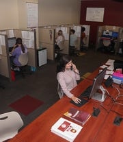 "Lauren Townsend, front, takes a call in the ""war room"" at Ace's Place at the University of Louisiana Monroe. Other students helping callers are, from left, Carson Wilkie, Reagan Lloyd, Carah Satre, Briana Webber and William Scott."