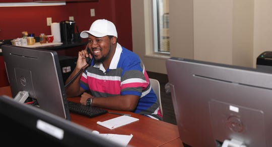"William Scott Jr. takes a call in the ""war room"" at ULM's Ace's Place. Student workers are trained to help callers get answers to their questions. ""It's always been a great feeling helping students whenever they call about any issue,"" he said."
