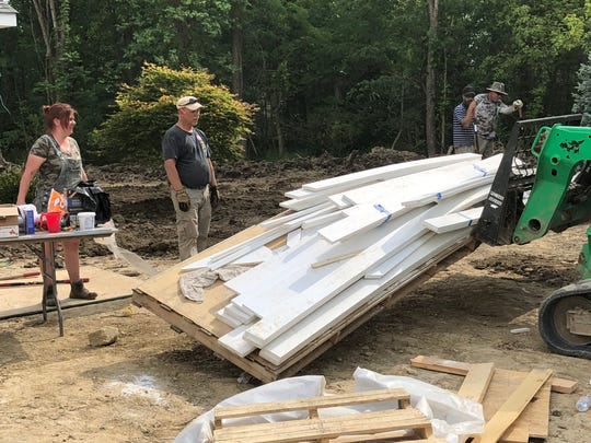 Cassie Garner and Don Tipton, both of Knoxville, Tennessee, wait as materials are unloaded for use on the smart home being built for disabled Marine Corporal Melroy Cort and his family.