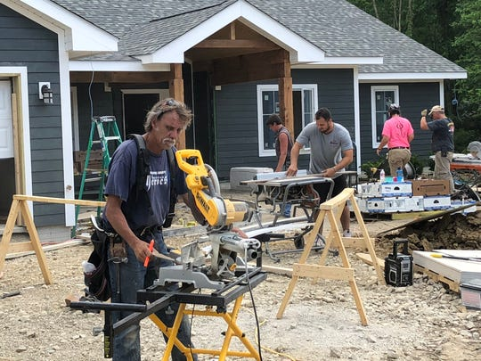 Chris Baktis of Long Island, New York (foreground) and Jerret Patterson of Augusta, Georgia (center) cut up materials for the new smart home built for disabled Marine Corporal Melroy Cort and his family.