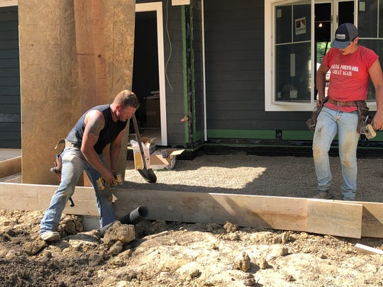 Volunteers from A Soldier's Journey Home work on the deck of the new smart home for disabled Marine Corporal Melroy Cort and his family.