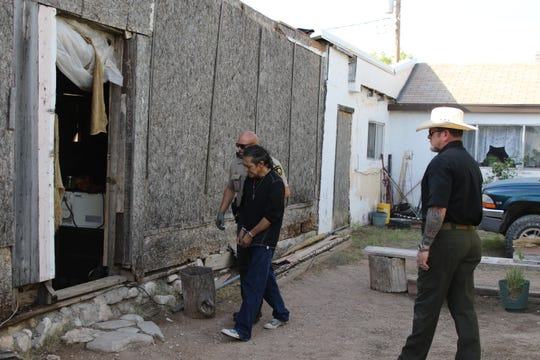 An unidentified Eddy County Sheriff's deputy leads Louie Ramos into a residence at the corner of Oklahoma and Monterrey Streets in Carlsbad during a June 12, 2020 drug raid. Eddy County Sheriff Mark Cage looks on.