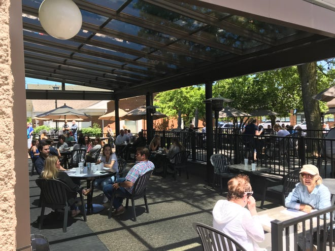 Diners eat outside Thursday afternoon on the patio of Poole's Tavern in downtown Northville.