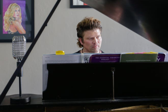 Austin Wenker, owner of Tempo Music Studio and Art Gallery, plays a piano in his store on Friday, June 5, 2020, in Oshkosh, Wis.
