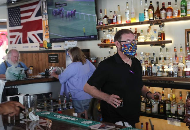Josh Osborne tends bar at The Hair of the Dog in Palm Springs on June 12, 2020. Gov. Gavin Newsom, on July 1, ordered bars in 19 counties to close again as part of his efforts to keep coronavirus at bay.