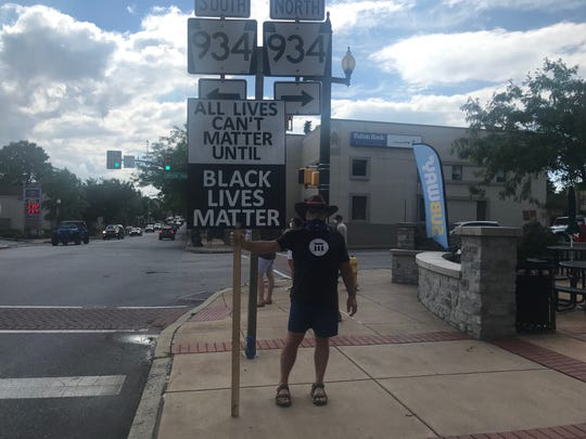 Lebanon Valley College professor Michael Schroeder holding his sign at the Annville square, the intersection of Route 934 and Route 422.