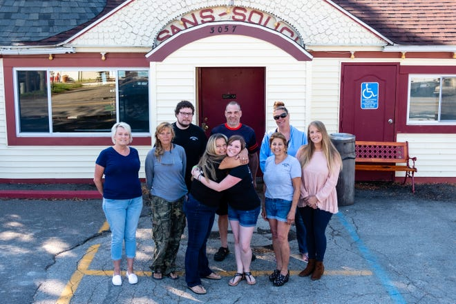 Former employees pose in front of Sans Souci Bar Friday, June 12, 2020, on Harsens Island. After operating for nearly 40 years, the bar has closed.