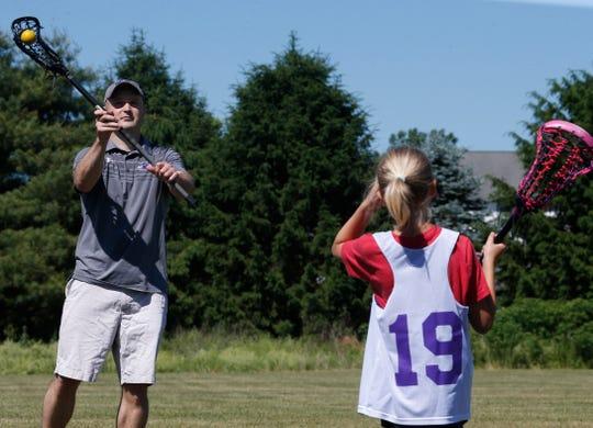 Dan Schmitt practices with his daughter Penney at Stringham Park in LaGrangveville on June 12, 2020.