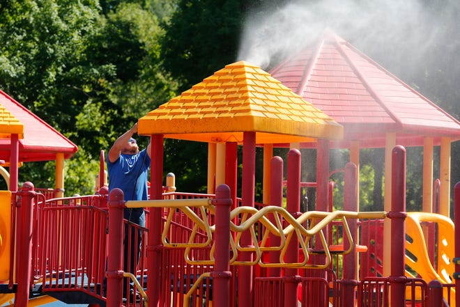 Richmond Parks and Recreation Department staff get the playground equipment at Glen Miller Park ready to reopen on Friday, June 12, 2020.