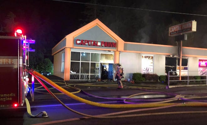 Crews worked late Thursday to extinguish a fire at Capital Pawn on Commercial Street in south Salem.