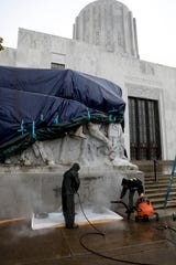 Adam Marcum, left, and Joe Bryson from Pioneer Waterproofing Company work to remove spray paint from a sculpture at the Oregon State Capitol in Salem, Oregon, on Friday, June 12, 2020.