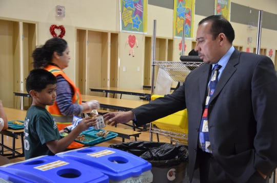 A young boy hands his chocolate milk carton to Roberto Rodriguez, Jesse G. Sanchez Elementary School principal, during lunch in Salinas, Calif.