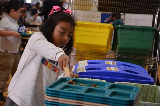 A young girl wearing a pink bow on her head throws her leftover food into a compost bin during her lunch period inside Jesse G. Sanchez Elementary School in Salinas, Calif.