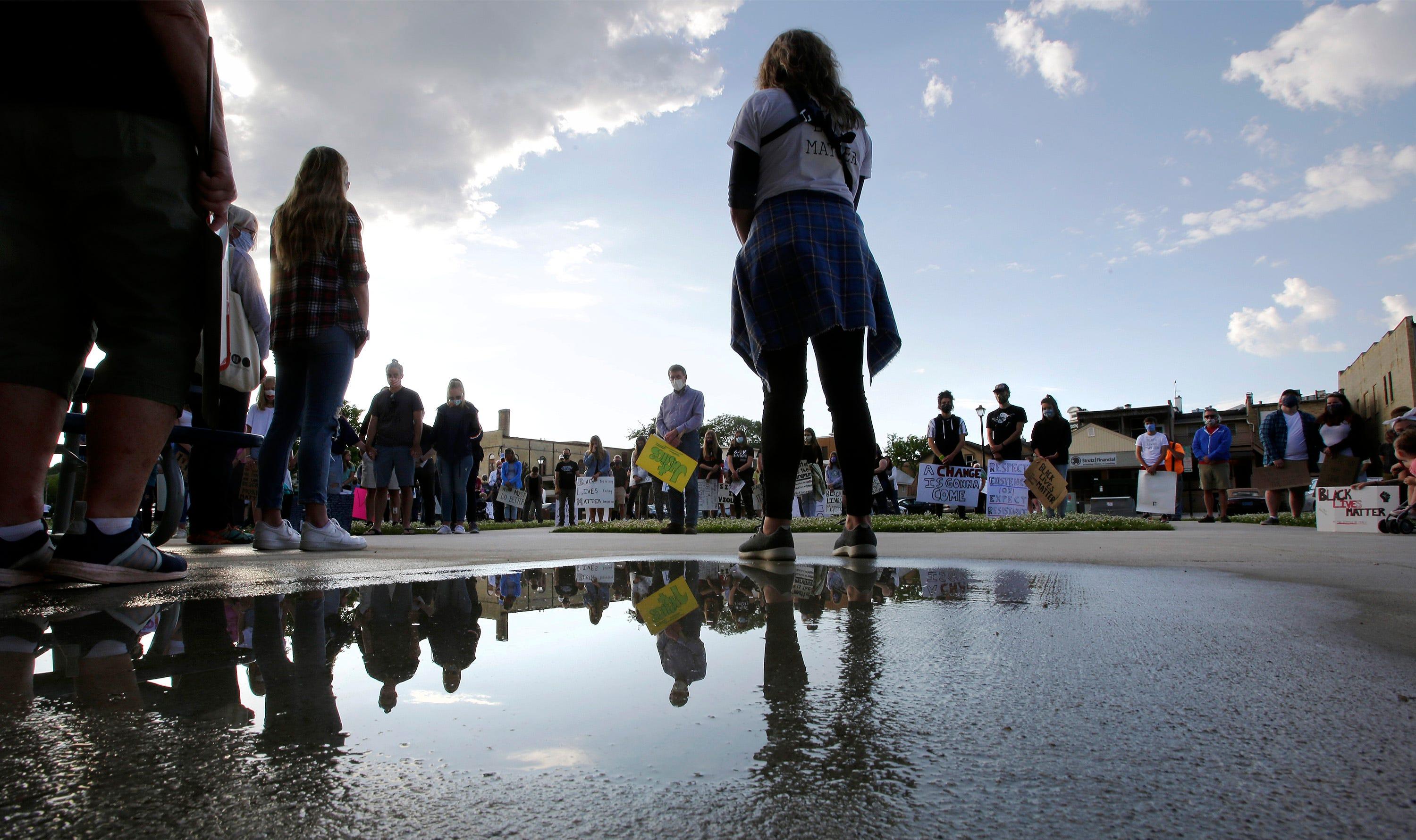 People are reflected in a water puddle during the time of silence during March for Justice, Black Lives Matter protest, Thursday, June 11, 2020, in Plymouth, Wis.