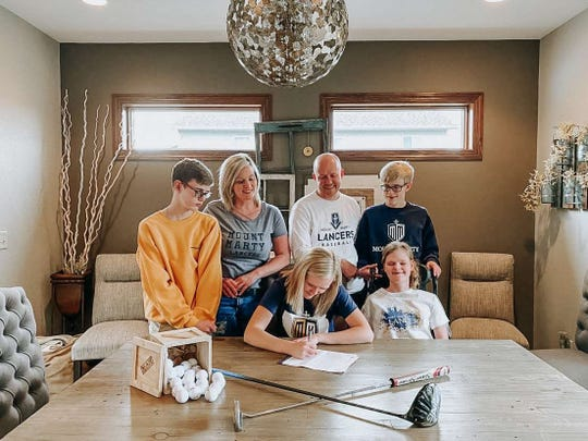 Tanna Lehfeldt (center) is surrounded by family as she signs with Mount Marty College earlier this year to play golf next season for the Lancers.