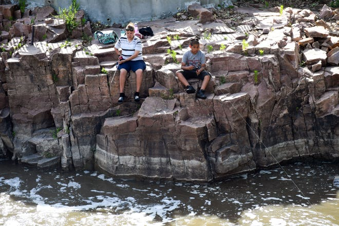 Taner Woodhull and Keiandrew Baxter fish on the Big Sioux River on Thursday, June 11, just below Falls Park in Sioux Falls.