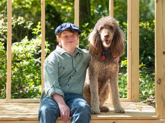 Charles Albury sits with his dog Banjo on an outdoor building project Charles is helping with in his backyard.