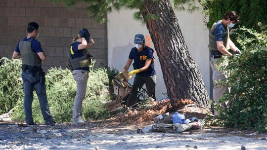 FBI agents examine an area in Paso Robles, Calif., Thursday, June 11, 202, as the investigation into the shooting of a sheriff's deputy early Wednesday continues in the Central Coast city. A man was found fatally shot near where the deputy was wounded, and authorities believe the events are connected. Deputy Nicholas Dreyfus was shot in the face. Authorities say he underwent successful surgery and his prognosis Thursday is good. Authorities have identified the suspect as 26-year-old Mason James Lira and they say he's a transient from the Monterey, Calif., area. (David Middlecamp/The Tribune of San Luis Obispo via AP)