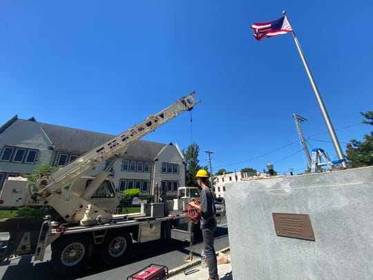 """Workers remove a statue of Christopher Columbus in Wilmington on Friday. The city said it would also take down one of Founding Father Caesar Rodney """"for an overdue discussion."""""""