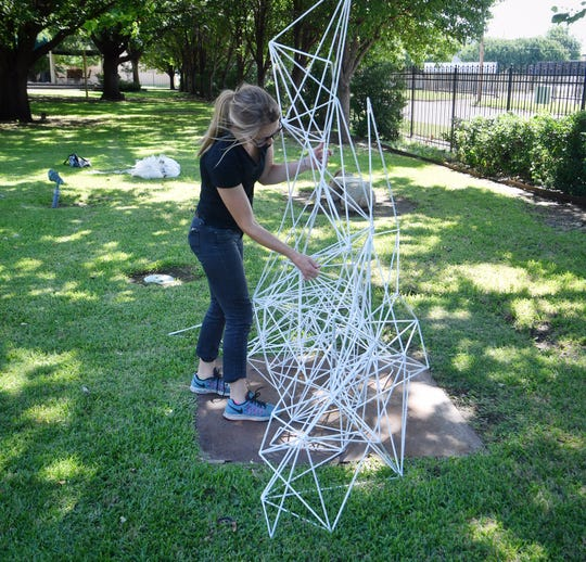 "Any Hoagland of Boulder, Colorado arranges her welded steel sculpture, ""Ice Frame"", as part of the new group of outdoor sculptures at the Kemp Center for the Arts Friday."