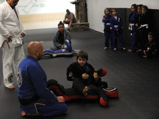 Instructor Jason Cable and his son, Brody, demonstrate on a grappling dummy during the youth class of the Gracie Allegiance Jiu-Jitsu Academy at Colony Square Mall.